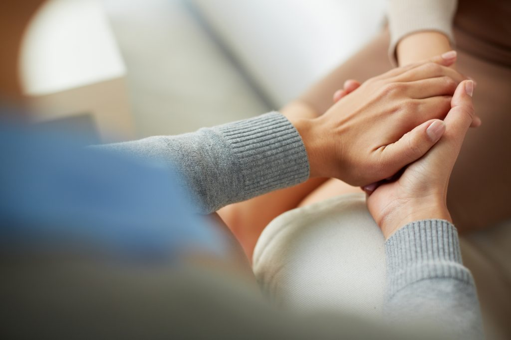 inner healing practitioner comforting a client holding their hand